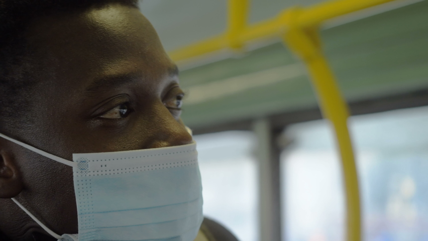 Young serious black man wearing the mask looks out the window on the subway | Shutterstock HD Video #1066175773