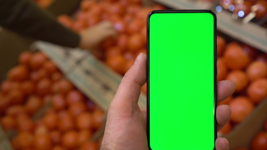 Back view of Man's hand, holding chroma key green screen smartphone watching content.Shopping center. Department store. Mall. Shopping online. Gadgets and contemporary people concept.   Shutterstock HD Video #1066179688