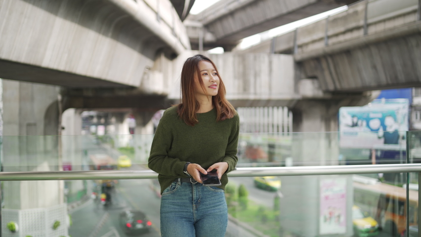 Young beautiful Asian woman walk in the city and using smartphone camera taking selfie or recording Vlog video with cityscape. Smiling female relax and enjoy city lifestyle with wireless technology. | Shutterstock HD Video #1066180417
