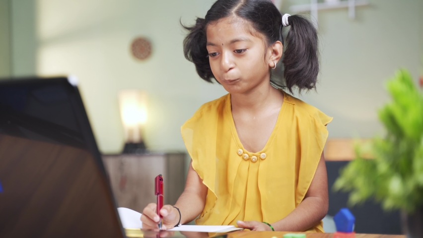 Concept of homeschooling, online education or e-learning, young girl busy in writing by looking into laptop while teacher explaining during class.   Shutterstock HD Video #1066180504