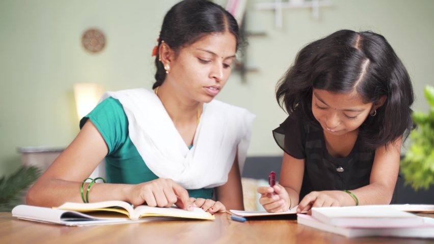 Concept of homeschooling, online education or e-learning, young girl busy in writing by looking into laptop while teacher explaining during class.   Shutterstock HD Video #1066180507