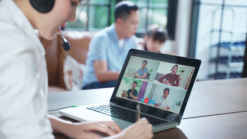 Asian business woman talking to colleague team about plan in video conference. Group of business people using computer for online meeting in video call conference. Smart working from home with family. | Shutterstock HD Video #1066181338