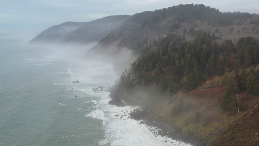 Mist drifts over the beautiful Northern California coastline in Klamath. The scenic Pacific Coast Highway runs along this amazing part of the west coast which is known for its extensive forests. Royalty-Free Stock Footage #1066181797