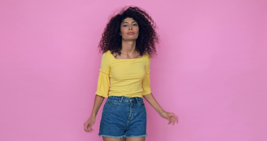 Cheerful young woman dancing isolated on pink | Shutterstock HD Video #1066184626