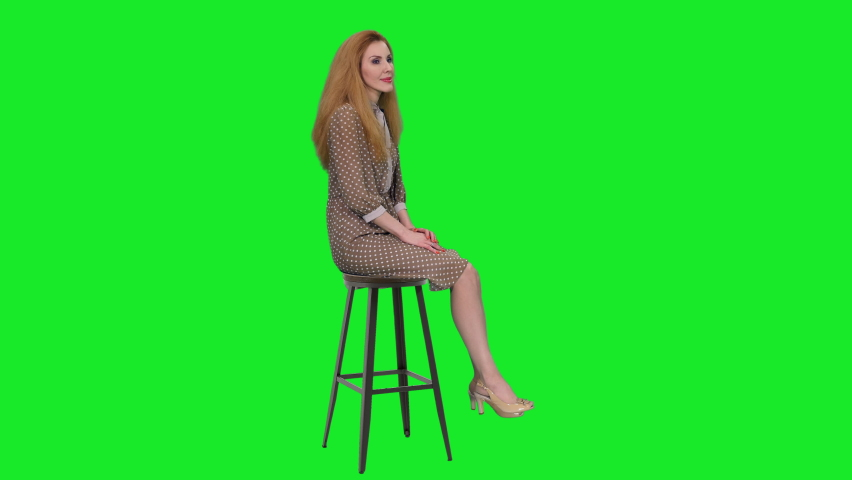 Elegant graceful woman with beautiful smile sitting on chair and telling a story to the audience against green screen background, chroma key 4k pre-keyed footage   Shutterstock HD Video #1066185259