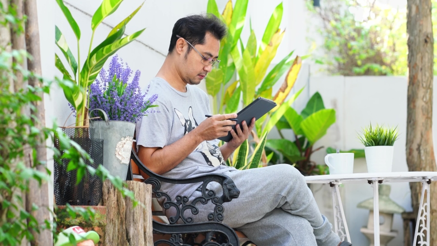 Business man sitting and drinking coffee Working happily with a holiday tablet in his backyard.   Shutterstock HD Video #1066189876