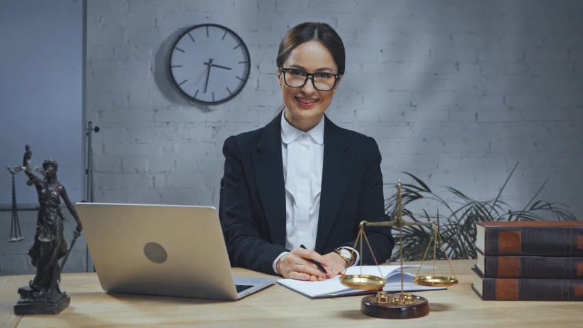 Smiling insurance agent sitting near laptop, scales and books | Shutterstock HD Video #1066193326