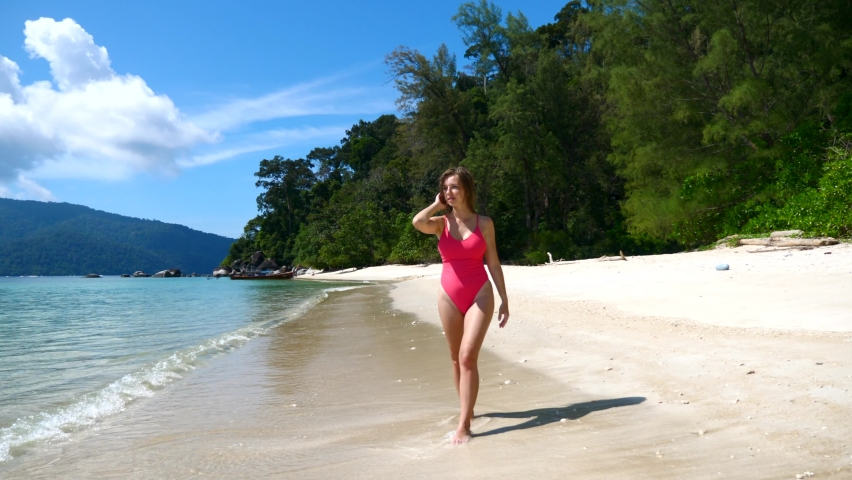 Sexy Young Woman in Red Swimwear Walking on Beach with White Sand and Blue Ocean Water at Hot Sunny Day. Woman Relax on Vacation Near Turquoise Sea in Tropics in Thailand | Shutterstock HD Video #1066194166