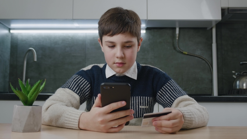 12-13 years old boy sitting at the kitchen table and shopping online with credit card and smartphone while sitting at home. Kid schoolboy with mobile phone using online payment systems. Online banking   Shutterstock HD Video #1066194220