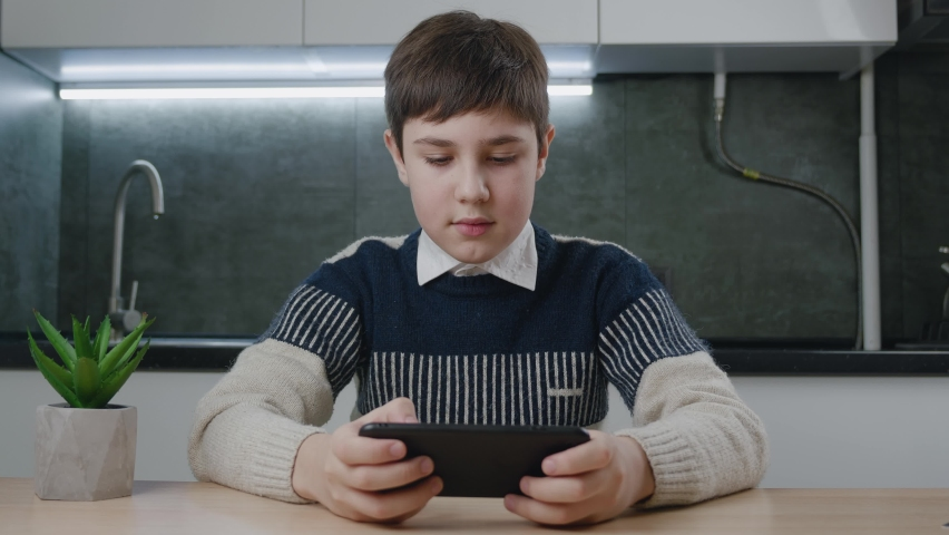 Portrait of handsome boy playing video game with smart phone indoors at living room. Kid 13 years old sitting at table and enthusiastically looking at the screen of his smartphone at home kitchen.   Shutterstock HD Video #1066194241