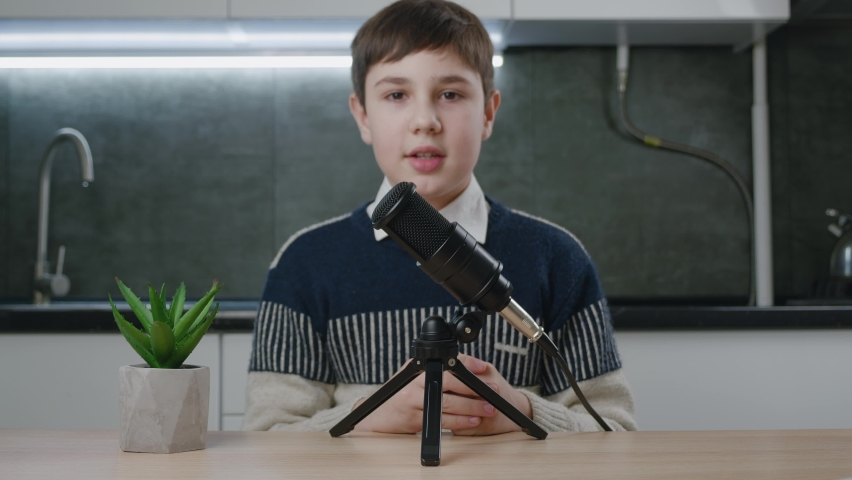 Boy vlogger look at camera and recording podcast video for internet. Kid videoblogger filming new vlog video with professional microphone at home. Young blogger talking on video shooting. | Shutterstock HD Video #1066194265