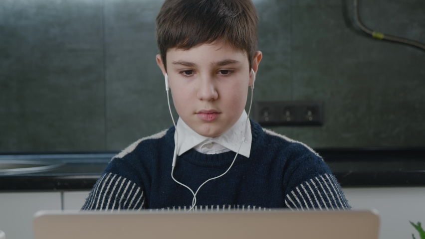 Portrait of teenage caucasian boy using laptop while studying at home. Schoolboy kid in earphones working on computer while sitting at living room | Shutterstock HD Video #1066194271
