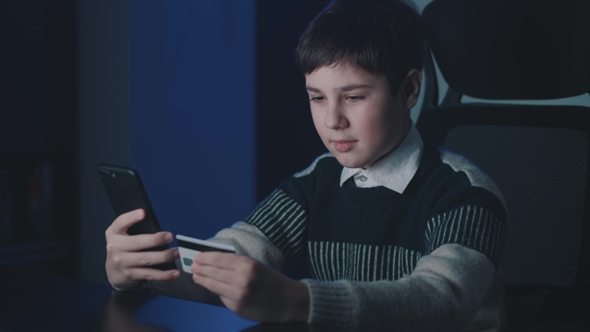 12-13 years old boy shopping online with credit card and smartphone while sitting at home late at night time. Kid schoolboy with mobile phone using online payment systems. Online banking.   Shutterstock HD Video #1066194286