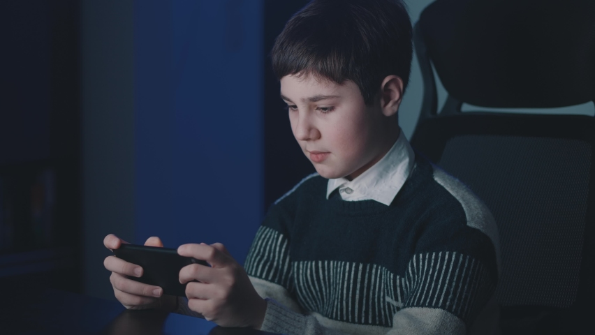 Portrait of handsome boy playing video game with smart phone indoors. Kid 13 years old sitting at table and enthusiastically looking at the screen of his smartphone at night home.   Shutterstock HD Video #1066194313