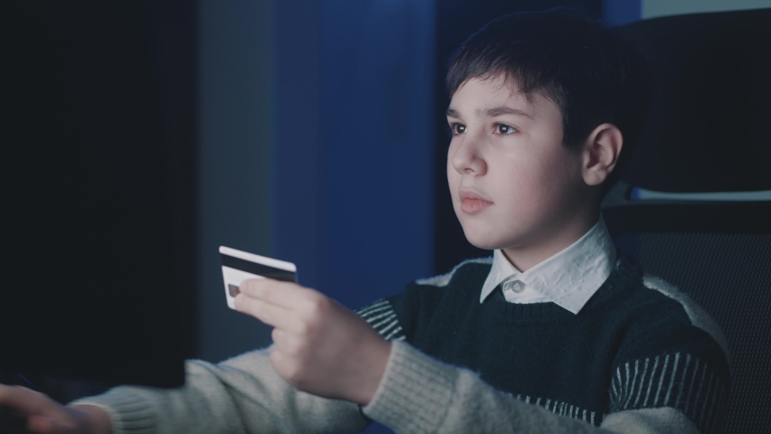 12-13 year old boy using computer laptop and shopping online with credit card while sitting at home late at night time. Kid shoolboy using online payment systems. Online banking.   Shutterstock HD Video #1066194334