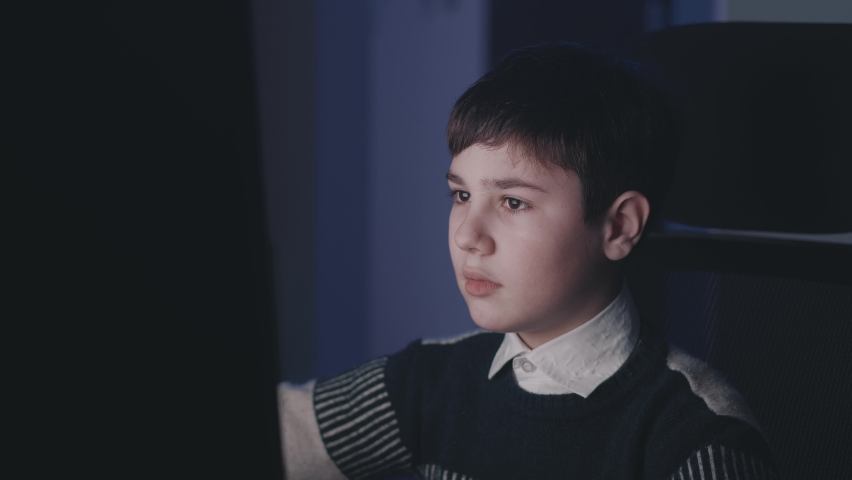 12-13 year old boy uses computer at night home. Child learning online. Preteen school kid watching video and using computer applications during online education. Monitor light reflection on his face | Shutterstock HD Video #1066194412