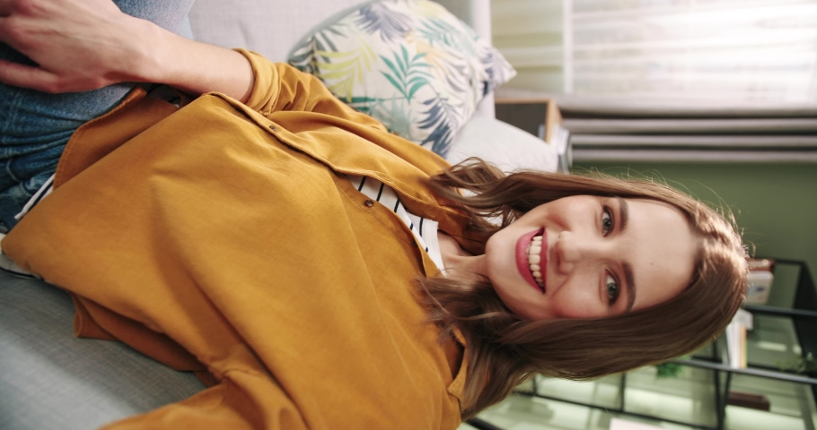 POV of Caucasian joyful smiling beautiful young woman sitting on sofa in cozy room recording video for blog. Female talks on video call through webcam at home and waving hand Close up Vertical concept Royalty-Free Stock Footage #1066196245