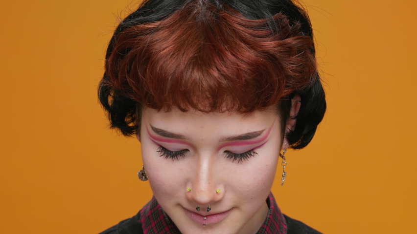 Portrait Teenage Girl Asian on Yellow Background with Piercings Cute Smiling With Bright Makeup Looks at the Camera Moving in Slow Motion Close-up. Joy. Positive emotions | Shutterstock HD Video #1066198564
