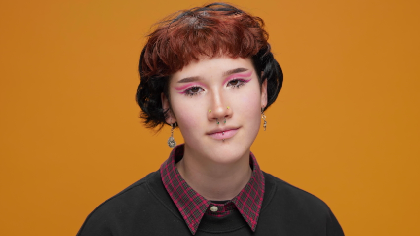 Portrait Teenage Girl Asian on Yellow Background with Piercings Cute Smiling With Bright Makeup Looks at the Camera Moving in Slow Motion Close-up. Joy. Positive emotions | Shutterstock HD Video #1066198567