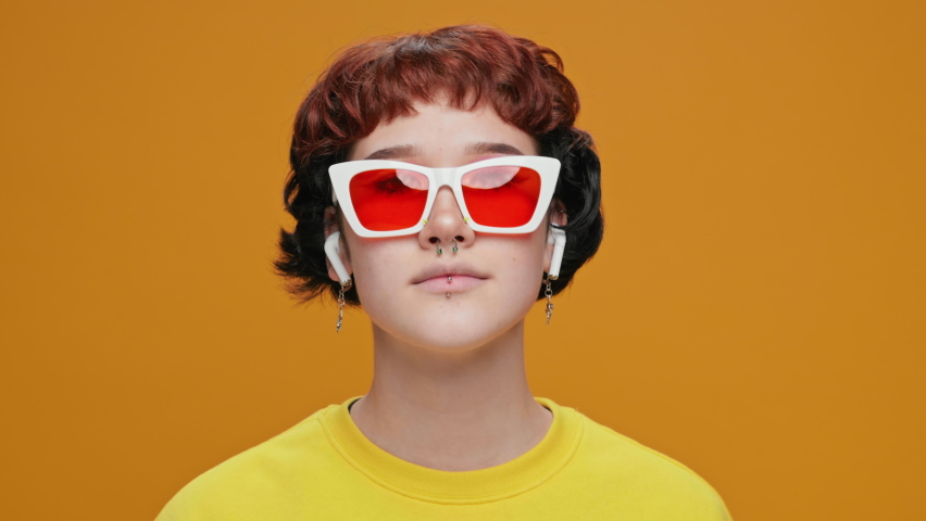 Dancing Girl Teenager Asian Listens to Music in Headphones from Smartphone on Yellow Background with Piercings in Glasses. Smiling with Bright Makeup moving slow motion. Positive emotions | Shutterstock HD Video #1066198573