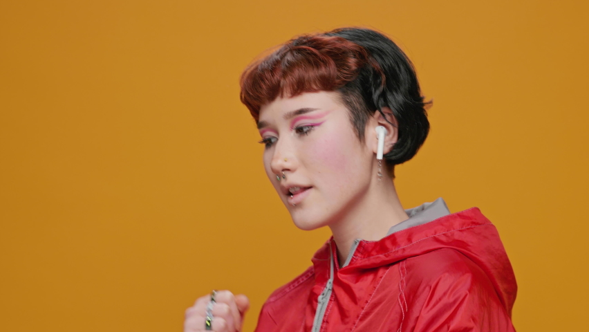 Dancing Teenage Girl Asian on Yellow Background Listening to Music in Red Hoodie in Glasses with Piercings Smiling Moving in Dance Sings slow motion. Joy. Positive emotions. Lifestyle. Bright make-up | Shutterstock HD Video #1066198576