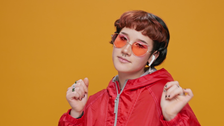 Dancing Teenage Girl Asian on Yellow Background Listening to Music in Red Hoodie in Glasses with Piercings Smiling Moving in Dance Sings slow motion. Joy. Positive emotions. Lifestyle. Bright make-up | Shutterstock HD Video #1066198579