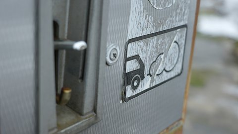 Closer look of the gasoline station pump with the brooken glass and the keyholes on it