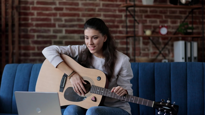 Female practicing and learning how to play guitar on laptop computer monitor. Girl guitarist watching online tutorial. Woman is looking at screen and playing guitar alone. Distance education concept. | Shutterstock HD Video #1066203433