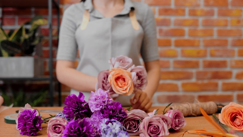 Slow motion. Brunette girl making bunch of flowers in flower store. Woman professional take flowers and makes bouquet. Close up young female florist in apron at workplace in flower shop. | Shutterstock HD Video #1066203580