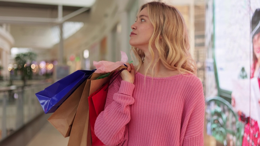 Blonde female in pink sweater walks around shopping mall with colorful shopping bags. Smiling girl looking to the side with colorful bags in hands after successful shopping at store. | Shutterstock HD Video #1066203595