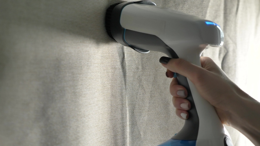 A woman's hand with a close-up manicure with the help of a modern steamer smoothes a crumpled fabric, cleans the house. | Shutterstock HD Video #1066204726
