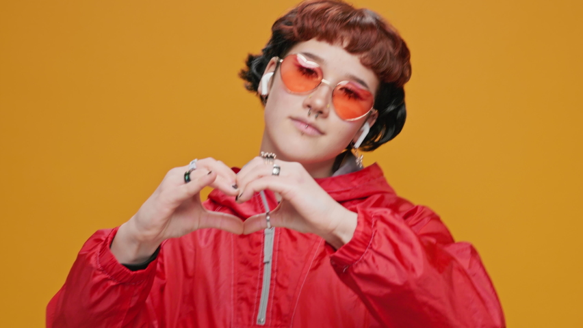 Portrait of Happy Teen Asian Girl Shows her Fingers Heart-shaped Sign and Presses to Chest in Yellow Sunglasses on Yellow Background Slow Motion. Emotions and Communication of People. Saint Valentine | Shutterstock HD Video #1066205239