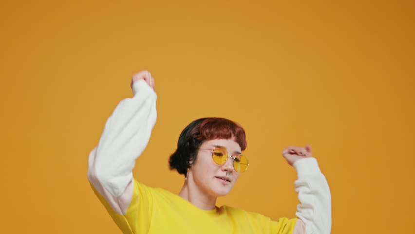 Teenage Girl Asian Jumping Up on Yellow Background with Piercings Rejoices Rhythmically Moving Her Hands Looks at the Camera Smiling Slow Motion Close-up. Positive emotions | Shutterstock HD Video #1066205248
