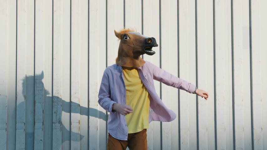 Dancing Funny Young Man in a Horse Mask Rhythmically Moving his arms Up on a Gray Background in the Street Slow Motion in Sunny Day. Crazy fun dancing Hipster. Happiness Holidays. Face Horse | Shutterstock HD Video #1066208578