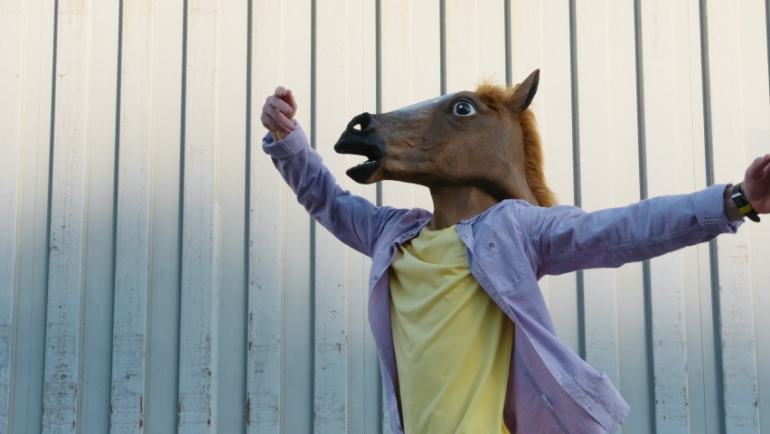 Dancing Funny Young Man in a Horse Mask Rhythmically Moving his arms Up on a Gray Background in the Street Slow Motion in Sunny Day. Crazy fun dancing Hipster. Happiness Holidays. Face Horse | Shutterstock HD Video #1066208581