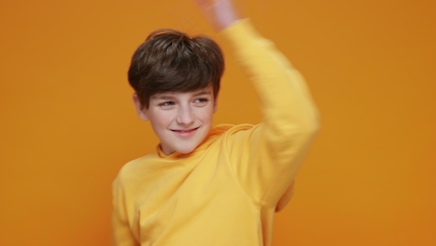 Happy Boy Jumping Up Smiling, Dancing Rhythmically Moving his arms up in a Yellow Jacket, Having Fun on a Yellow Background Looking at the Camera Slow Motion. Funny dances. Childhood. Children | Shutterstock HD Video #1066208587