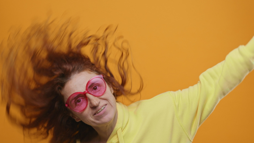 Dances Happy Young Woman Joyfully, Long Red Hair Develops from side to Side Yellow Background, shakes her Head and Rhythmically Moves Her Hands to Music Sings Slow Motion. Positive Emotion. Freedom | Shutterstock HD Video #1066208590