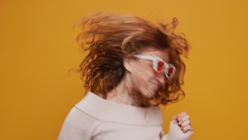 Dances Happy Young Woman Joyfully, Long Red Hair Develops from side to Side Yellow Background, shakes her Head and Rhythmically Moves Her Hands to Music Sings slow motion. Positive Emotion. Freedom | Shutterstock HD Video #1066208596