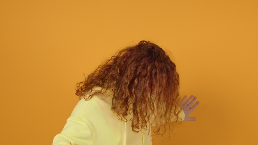 Dancing Happy Young Woman Joyfully, Long Red Hair Develops from side to Side Yellow Background, shakes her Head and Rhythmically Moves Her Hands to Music Sings. Positive Emotion. Freedom. Monotone | Shutterstock HD Video #1066208602