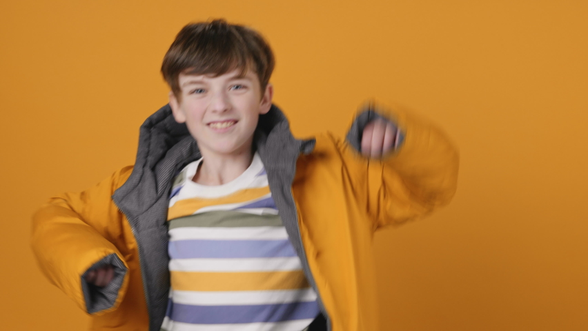Happy Boy Jumping Up Smiling, Dancing Rhythmically Moving his arms up Yellow Jacket, Having Fun on Yellow Background Looking at Camera Slow Motion. Funny dances. Childhood. Positive Emotion. Monotone | Shutterstock HD Video #1066208605