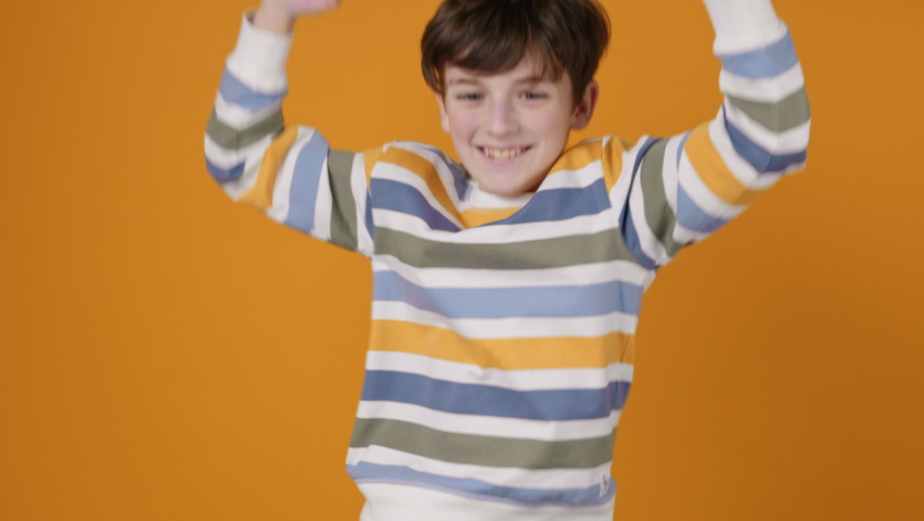 Happy Boy Jumping Up Smiling, Dancing Rhythmically Moving his arms up, Having Fun on a Yellow Background Looking at the Camera Slow Motion. Funny dances. Positive Emotion. Freedom Childhood. Children | Shutterstock HD Video #1066208608