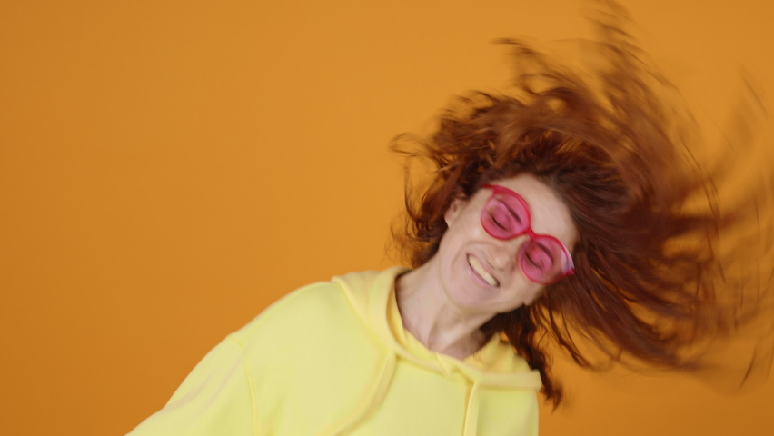 Dances Happy Young Woman Joyfully, Long Red Hair Develops from side to Side Yellow Background, shakes her Head and Rhythmically Moves Her Hands to Music Sings slow motion. Positive Emotion. Freedom | Shutterstock HD Video #1066208611