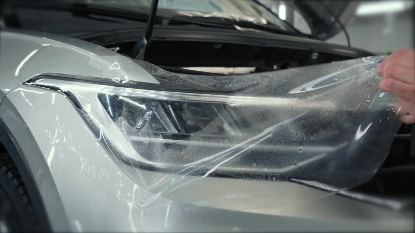 Process of installing of Paint Protection Film or PPF on new car in professional auto Detailing Center. Thin polyurethane film or polymer as protective skin from scratches and rock chips | Shutterstock HD Video #1066209106