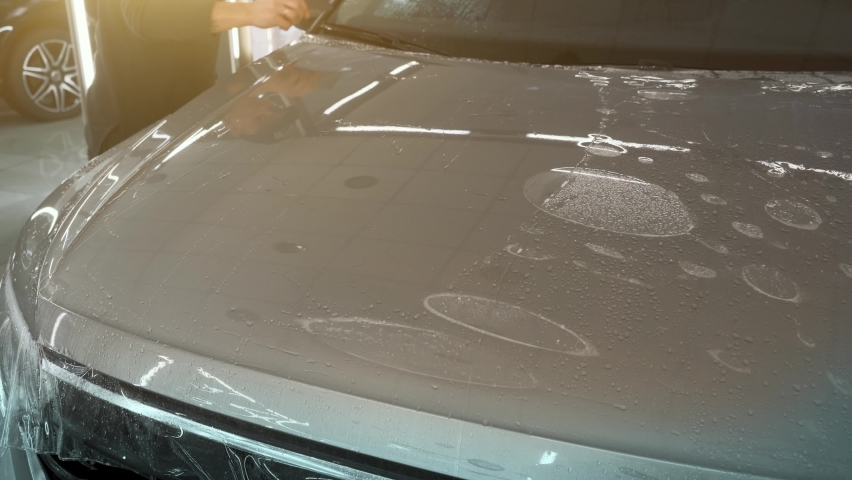 Process of installing of Paint Protection Film or PPF on new car in professional auto Detailing Center. Thin polyurethane film or polymer as protective skin from scratches and rock chips | Shutterstock HD Video #1066209124