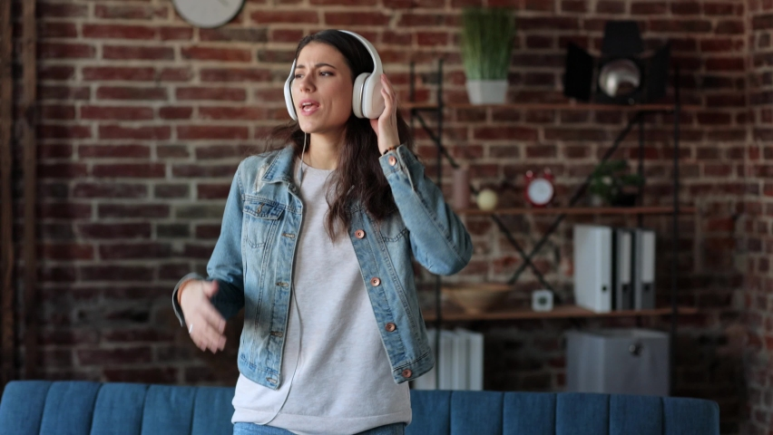 Female dancing. Slow motion. Happy young woman wear wireless headphones listening to music pretending playing guitar relaxing after work. Brunette girl having fun at home. | Shutterstock HD Video #1066209169