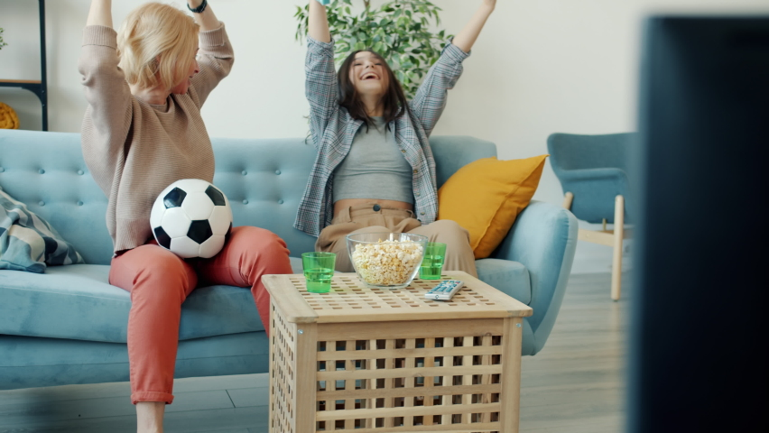 Mother and teenage daughter are watching sports on TV cheering then doing high-five celebrating victory and laughing sitting on couch at home | Shutterstock HD Video #1066210135