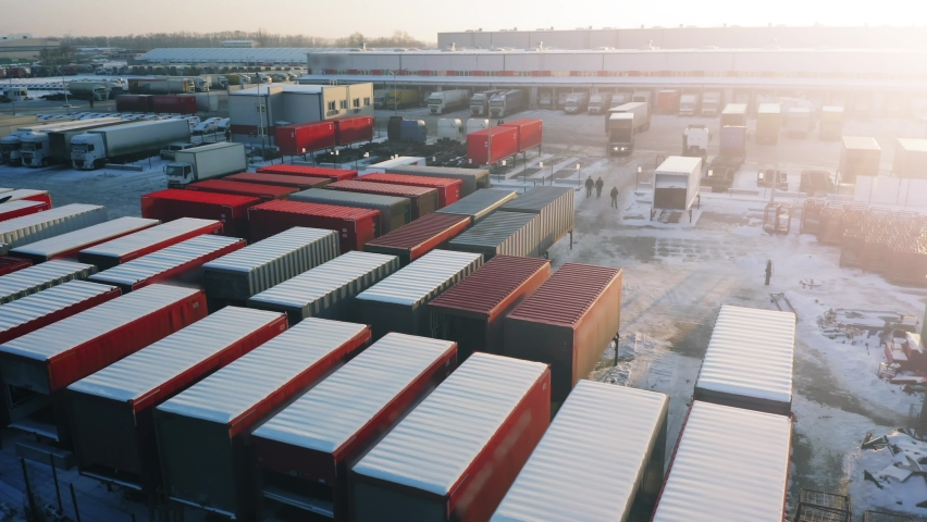 Cargo containers stand on the parking lot of the logistics park. Snow covered freight containers and semi-trailers trucks stand outside the warehouse in loading hub. Aerial view on a winter day | Shutterstock HD Video #1066212037
