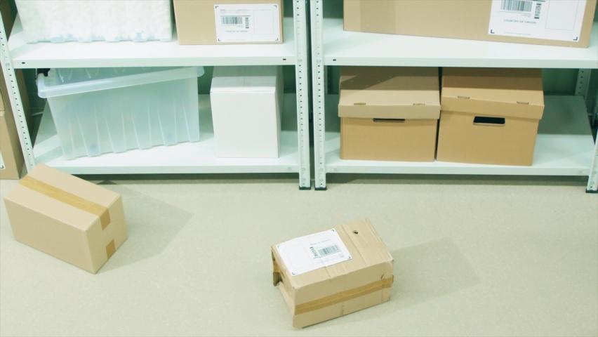 Neglectful warehouse worker kicks a parcel on the storage floor, slow motion shot | Shutterstock HD Video #1066213912