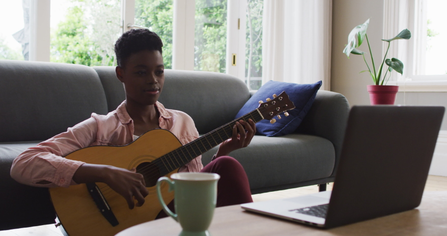 African american woman playing guitar while looking at laptop at home. lifestyle living self isolating in quarantine lockdown | Shutterstock HD Video #1066216039