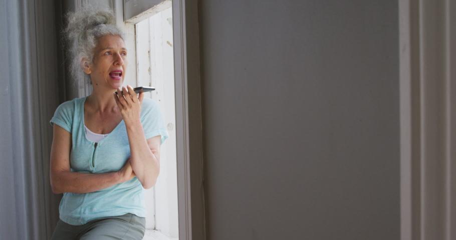 Senior caucasian woman talking on smartphone near the window at home. retirement senior couple lifestyle living self isolating in quarantine lockdown